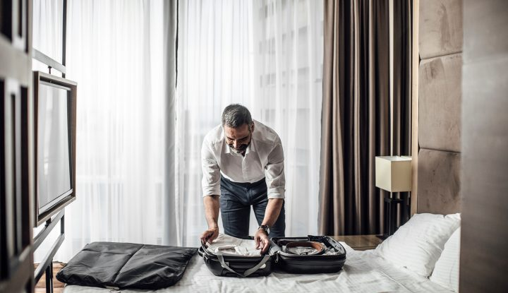 Business man packing suitcase in hotel room