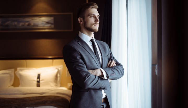Hotelier in suit looking out window